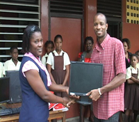 Principal Violine Christopher receives the computer equipment from Mr. Darroux