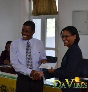 Mrs. Suzanne Piper (right) Handing check over to Minister of Education Mr. Petter Saint-Jean.
