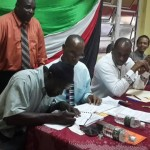 Matthew Gustave signs contact while Prime Minister Skerrit, ParlRep Drigo and PS Letang look-on